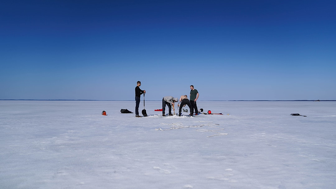 Drilling a ice hole for ice swimming in Finland. VIKINGS.